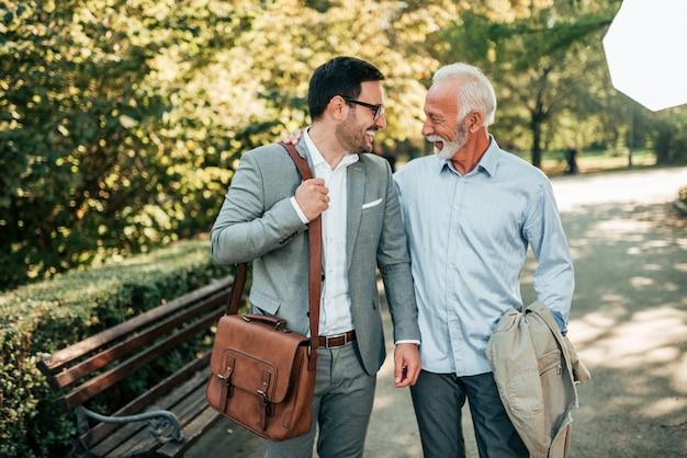 Due uomini eleganti che camminano nel parco.
