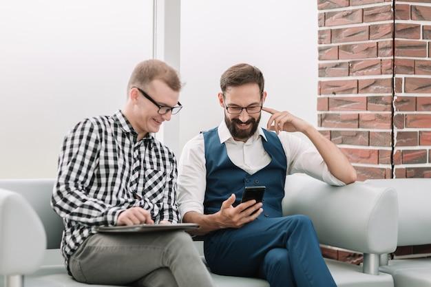 Due dipendenti che guardano lo schermo dello smartphone