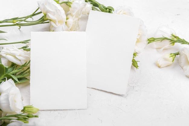 Due mockup di carte 5x3,5 vuote con fiori di eustoma lisianthus bianchi in fiore, elemento di design per invito a nozze, grazie o biglietto di auguri. sfondo primaverile