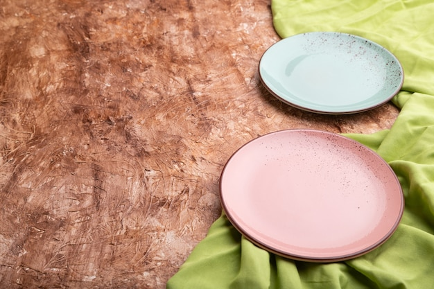 Due piatti blu e rosa vuoti su fondo di cemento marrone e tessuto verde. vista laterale,