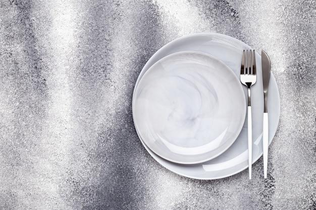 Due piatti di ceramica vuoti e coltello inutilizzato con forchetta, stoviglie su un tavolo grigio grunge, concetto di servizio. design piatto. menù del caffè. biglietto di auguri, layout, mockup con copia spazio. vista dall'alto. modello.