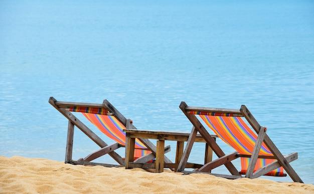 Due sedie colorate vuote dell'imbracatura del salotto della tela e tavolo di legno sopra il mare blu