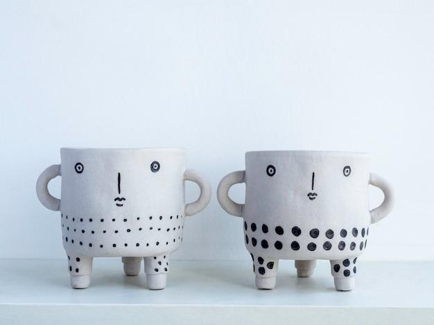 Due vasi per piante in ceramica con viso carino vuoto su ripiano in legno bianco isolato su parete bianca con spazio per copia. piccola moderna fioriera in cemento fai da te decorazione alla moda.