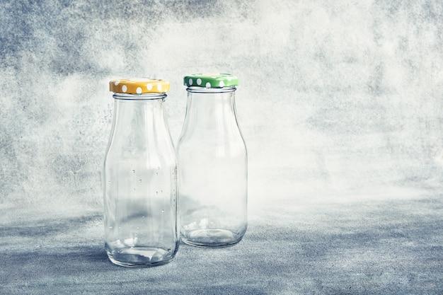 Due bottiglie di vetro vuote con coperchio colorato su sfondo grigio spazio copia
