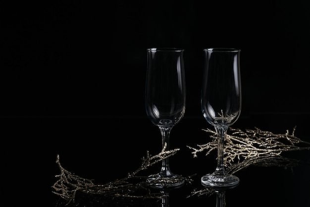 Due bicchieri vuoti di champagne e decorazioni di natale o capodanno su uno sfondo nero. cena romantica. concetto di vacanza invernale.