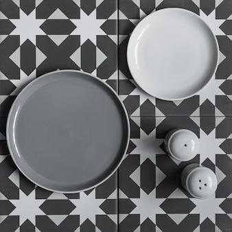 Due piatti rotondi grigi vuoti su una tavola grafica - disegno marrone e bianco. peperoncino e barretta