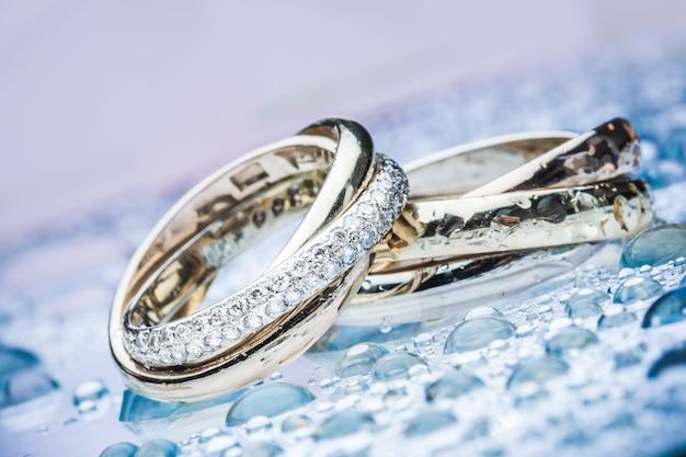 Due anelli di fidanzamento in platino e oro con diamante sullo sfondo da vicino