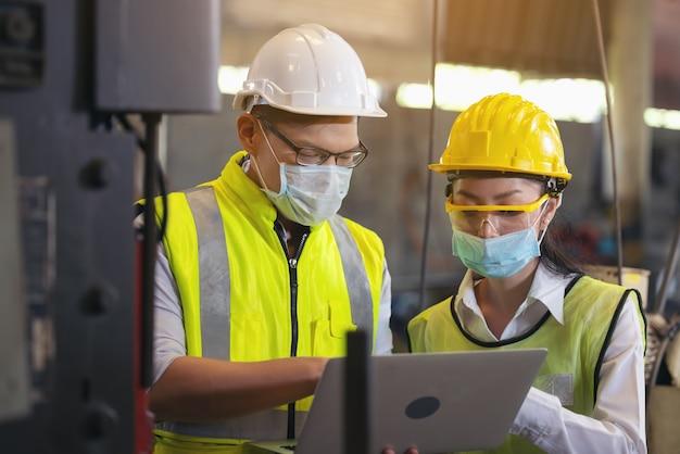 Due ingegnere in elmetto che indossa la sicurezza utilizzando il computer portatile per la pianificazione di un progetto.