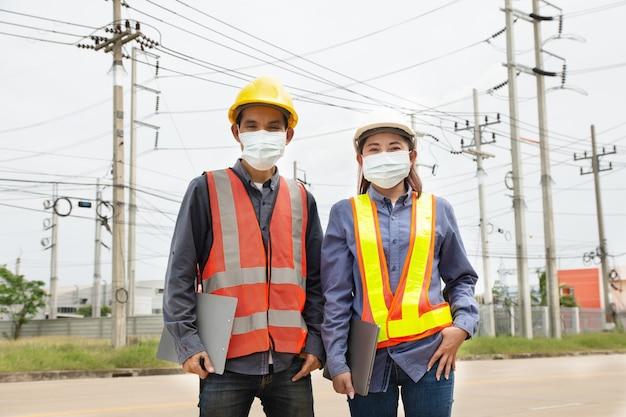 Il lavoro di squadra di due ingegneri indossa una maschera per proteggere il coronavirus covid19