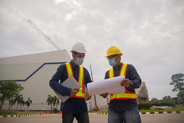 Progetto di lavoro di squadra di due ingegneri durante la costruzione del sito, maschera facciale da indossare per proteggere il covid19, architetto professionista del lavoro dei lavoratori