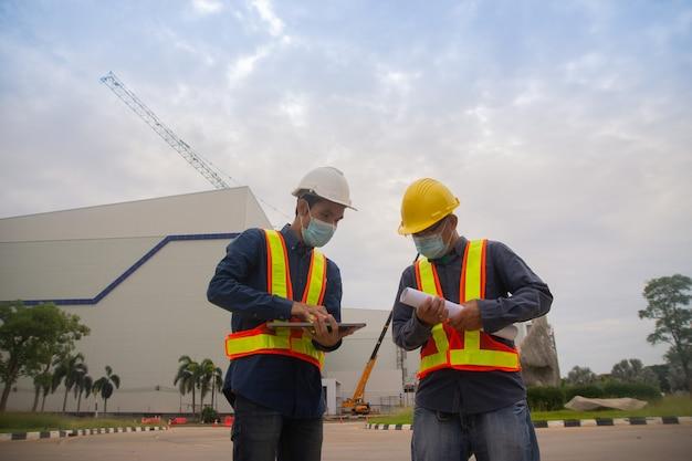 Due ingegneri che lavorano la tecnologia informatica sulla costruzione del sito, la maschera da indossare due ingegneri protegge il covid19vid