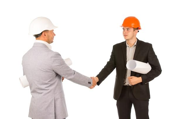 Due ingegneri in abbigliamento grigio e nero che stringono la mano isolati su sfondo bianco.
