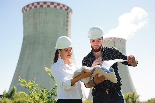 Due ingegneri in piedi alla stazione elettrica, discutendo il piano.