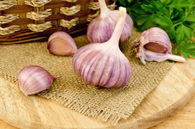 Due teste intere e tre spicchi d'aglio, un cesto di vimini, un mazzetto di prezzemolo verde su una tavola di legno e un tovagliolo di tela