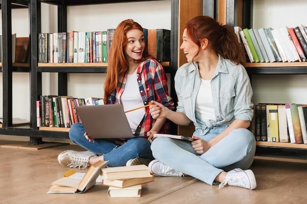 Due adolescenti eccitati che si siedono su un pavimento