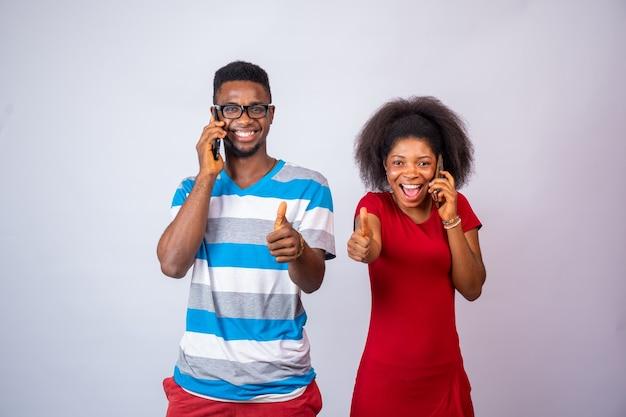 Due giovani africani eccitati che fanno telefonate, in piedi sul bianco, danno i pollici in su