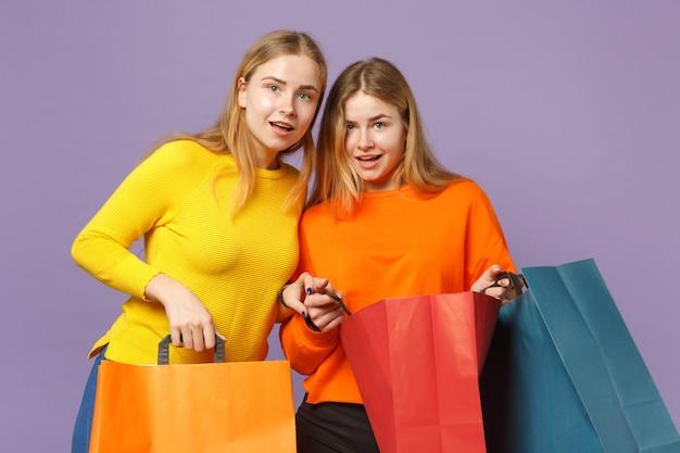Due giovani sorelle gemelle bionde eccitate in abiti vivaci che tengono la borsa del pacchetto con gli acquisti dopo lo shopping isolato sulla parete blu viola. concetto di stile di vita familiare di persone. .