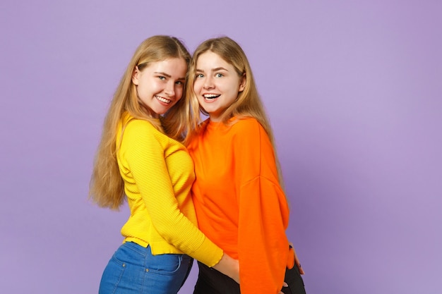 Due giovani sorelle gemelle bionde eccitate in abiti colorati vividi in piedi, isolate sulla parete blu viola pastello. concetto di stile di vita familiare di persone.