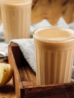 Due bicchieri di vetro sfaccettati su un tavolo di legno con la tradizionale bevanda indiana masala chai.