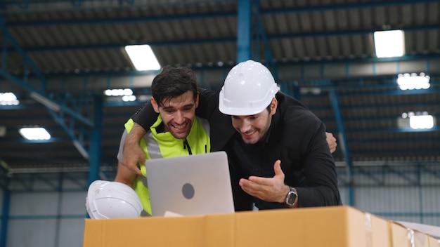 Due operai celebrano insieme il successo in fabbrica o in magazzino. concetto di successo del lavoro di industria.