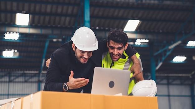 Due operai festeggiano insieme il successo in fabbrica