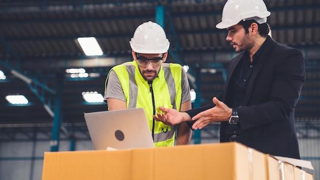 Due operai che lavorano e discutono del piano di produzione in fabbrica. concetto di industria e ingegneria.