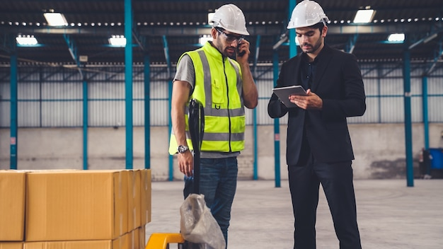 Due operai che lavorano e discutono del piano di produzione in fabbrica