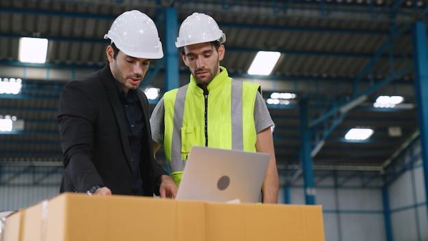 Due operai che lavorano e discutono del piano di produzione in fabbrica.