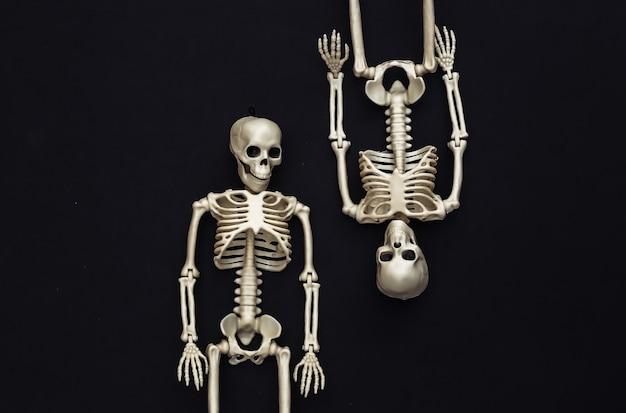 Due scheletri falsi su fondo nero. decorazione di halloween, tema spaventoso