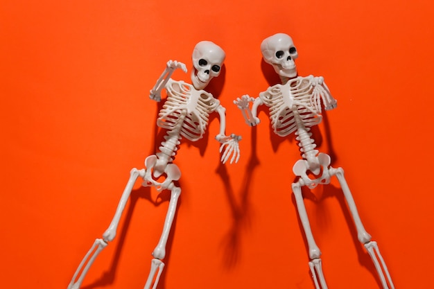 Due scheletri falsi su arancione brillante. decorazione di halloween, tema spaventoso