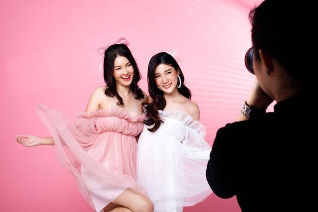 Two fashion beauty women ha i capelli neri che saltano ed esprimono un sorriso. le ragazze asiatiche indossano un abito rosa su un muro di tonalità rosa con muro di pomeriggio ombra striscia di finestra, copia spazio