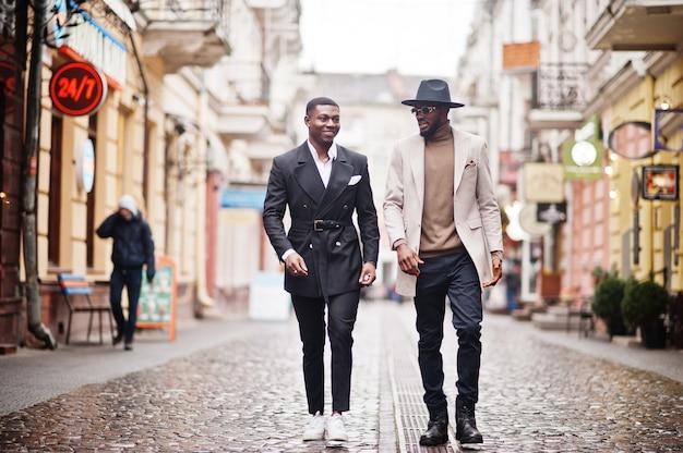Due uomini di colore di moda che camminano sulla strada. ritratto alla moda di modelli maschii afroamericani. indossa abito, cappotto e cappello.