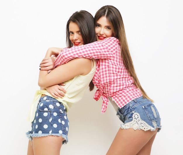 Due amiche dipinte di risate di moda che si abbracciano e si divertono su sfondo bianco.