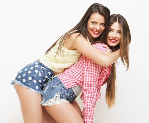 Due amiche dipinte di risate di modo che abbracciano e si divertono su sfondo bianco.