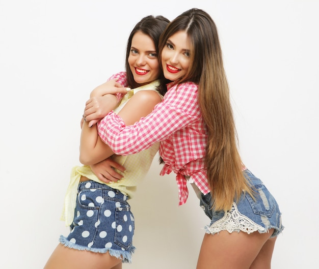 Due amiche dipinte di risate di moda che si abbracciano e si divertono. su sfondo bianco.