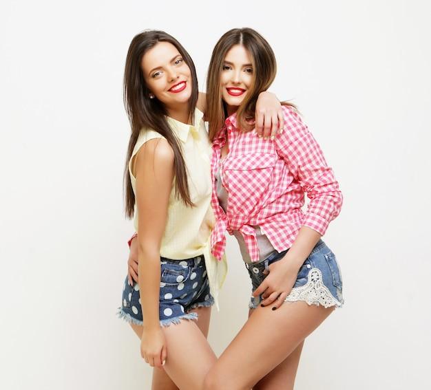 Due amiche dipinte che ridono alla moda si abbracciano e si divertono