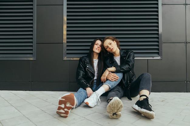 Due ragazze alla moda in abiti eleganti seduti per terra