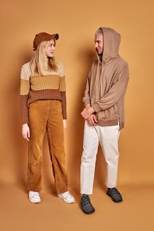 Due uomo alla moda e donna che si guardano sorridendo, indossando abiti alla moda, ritratto