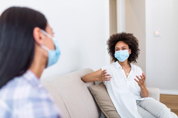 Due migliori amiche donne sedute a distanza sociale indossando la maschera e parlando sul divano, prevenendo la diffusione dell'infezione da coronavirus 19.