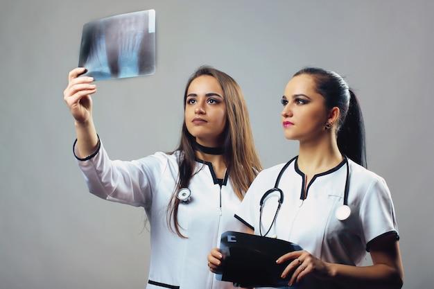 Due dottoresse guardando i raggi x. il concetto di salute, medicina e radiologia