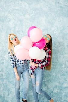 Due amiche in camicie a scacchi si divertono con i palloni ad aria sullo sfondo della parete blu