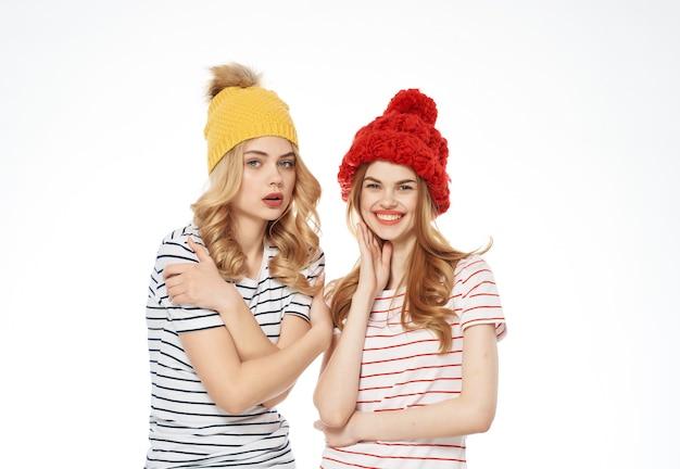 Due amiche in cappelli colorati sono in piedi uno accanto all'altro in posa sfondo chiaro. foto di alta qualità
