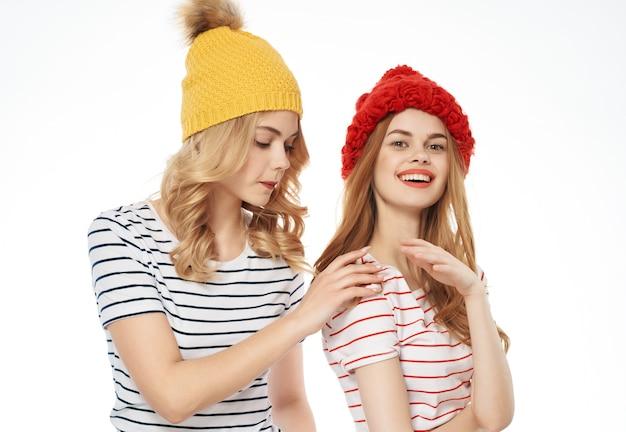 Due amiche con cappelli colorati sono in piedi l'una accanto all'altra in posa di sfondo chiaro