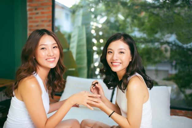 Due amiche fanno una manicure. il concetto di cura delle mani.