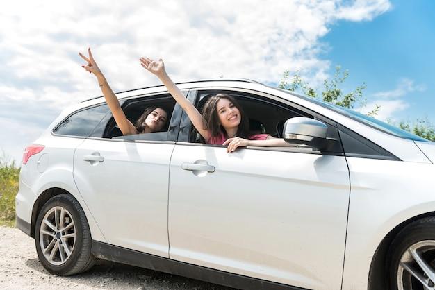 Due amici femminili seduti all'interno dell'auto per il miglior viaggio