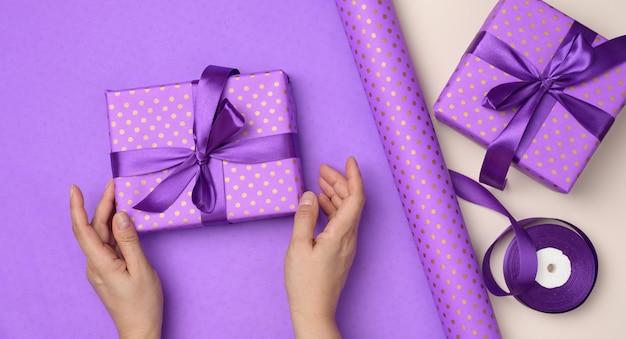 Due mani femminili tengono in mano una confezione regalo viola su sfondo di carta, concetto di congratulazioni per il compleanno, vista dall'alto