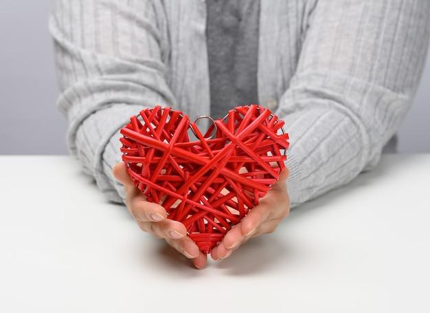 Due mani femminili tengono in mano un cuore di vimini rosso. concetto di gentilezza e amore, san valentino