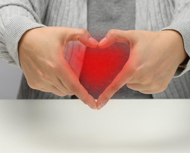 Due mani femminili piegate a forma di cuore su sfondo bianco. concetto di gratitudine e gentilezza, spazio di copia
