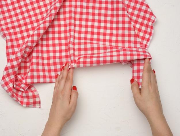 Due mani femminili tengono un tovagliolo da cucina in tessuto a scacchi bianco-rosso accartocciato su un tavolo bianco, vista dall'alto