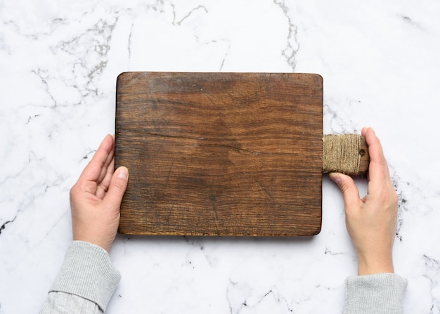 Due mani femminili tengono un tagliere di legno rettangolare marrone vecchio vuoto, fondo bianco, vista dall'alto